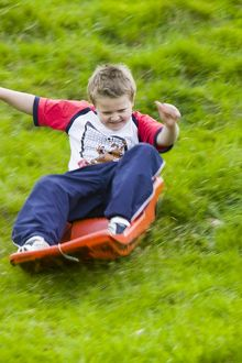 A young boy sledging down a grassy bank